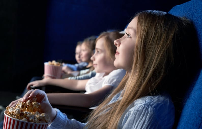 Four kids watching a movie at the cinema