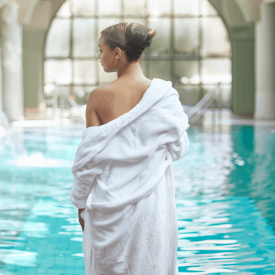 Lady in a white gown standing by the spa pool